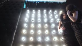 Two beautiful young fashionable female models posing in a studio against a wall background with many lamps. The view of the camera. Rises from feet to head.n stock video