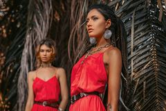 Two beautiful young fashionable models in red dresses outdoors at sunset. Two beautiful young fashionable models in red dresses outdoors stock photography