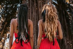 Two beautiful young fashionable models in red dresses outdoors at sunset. Two beautiful young fashionable models in red dresses outdoors royalty free stock photo