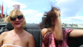 Two beautiful young female friends having fun riding in convertible stock video