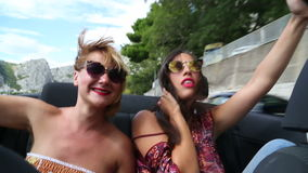 Two beautiful young female friends having fun riding in convertible. Two beautiful young female friends having fun riding in the back seat of convertible stock video footage