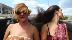 Two beautiful young female friends having fun riding in convertible. Two beautiful young female friends having fun riding in the back seat of convertible stock video