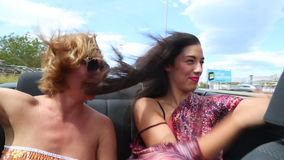 Two beautiful young female friends having fun riding in convertible stock video footage