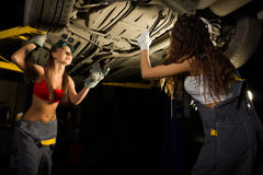 Two Beautiful young female mechanic inspecting car in auto repair shop. Sexy mechanic Royalty Free Stock Photography