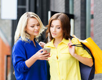 Two beautiful young female shopaholics Stock Photos