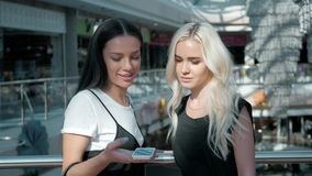 Two beautiful young female shopaholics surfing the internet in search of discounts in shopping mall, young student girls stock video footage