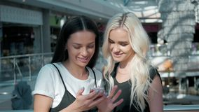 Two beautiful young female shopaholics surfing the internet in search of discounts in shopping mall, young student girls Royalty Free Stock Image