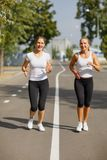 Attractive and smiling girls runners on a park background. Morning jogging. Running concept. Royalty Free Stock Images