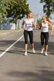 Attractive and smiling girls runners on a park background. Morning jogging. Running concept. Royalty Free Stock Photo