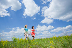 Two beautiful young friendly women walking. On summer field stock image