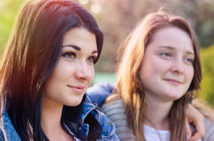Two beautiful young friends posing arm in arm. Looking at the camera with friendly smiles, close up portrait of their faces Stock Images