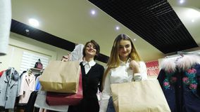 Two beautiful young girls with bags in their hands go through the store. They are happy with their purchases stock video