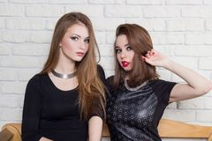 Two beautiful young girls in black dresses sit on the bench and gossip Royalty Free Stock Photography