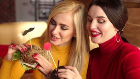 Two beautiful young girls with bright make-up eat burgers in a cafe. Portrait of two girls with burgers in their hands. Close-up. Slow motion. Fast food stock video footage