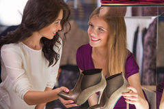 Two beautiful young girls choosing shoes at store Royalty Free Stock Image