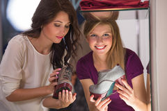 Two beautiful young girls choosing shoes at store Royalty Free Stock Images