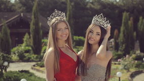 Two beautiful young girls in crowns and evening. Dresses posing in green park stock video