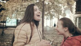 Two beautiful young girls are dancing on a city street at night. Mom and daughter dance listening to music in headphones. Two young girls listen to music on stock video footage