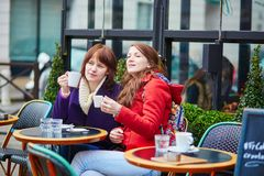 Two beautiful young girls drinking coffee Stock Photography