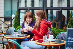 Two beautiful young girls drinking coffee Royalty Free Stock Image