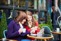 Two beautiful young girls drinking coffee Royalty Free Stock Images