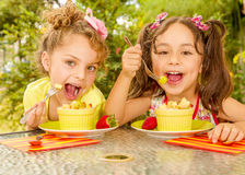 Two beautiful young girls, eating a healthy pineaple and grapes using a fork, in a garden background Stock Photo