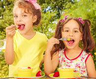 Two beautiful young girls, eating a healthy strawberry and grapes using a fork, in a garden background Royalty Free Stock Images