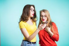 Two beautiful young girls are exploring the smartphone. Technologies stock photography