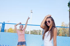 Two beautiful young girls on the floor of an empty pool Royalty Free Stock Photography