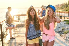 Two beautiful young girls having fun at the evening seaside with group of their friends on background stock photos