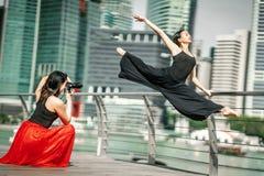 Two beautiful young girls having fun photo shooting on a deck wi stock photo