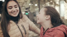 Two beautiful young girls include music through a smartphone and begin to dance. Mom and daughter dance in the middle of. The street listening to music on stock video
