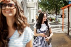 Two beautiful young girls with long dark hair,wearing casual outfit, walk down the street on a sunny day, royalty free stock photography