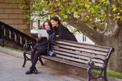 Two beautiful young girls look at photos on your tablet , socializing and shopping online Stock Images