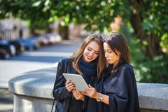 Two beautiful young girls look at photos on your tablet , socializing and shopping online Stock Photography