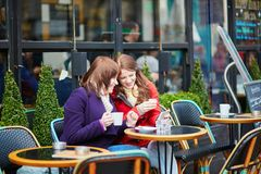 Two beautiful young girls in a Parisian cafe Royalty Free Stock Photo
