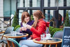 Two beautiful young girls in a Parisian cafe Stock Image