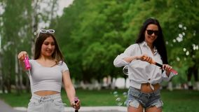 Two beautiful young girls in the Park are laughing while riding a Segway in the Park, blowing bubbles in slow motion.  stock video