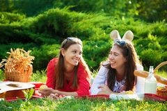 Two beautiful young girls at a picnic in the summer in the park having fun and talking Copy space stock photography