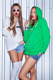 Two beautiful young girls with red lollipops near the wall Stock Photography