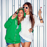 Two beautiful young girls with red lollipops near the wall Stock Image