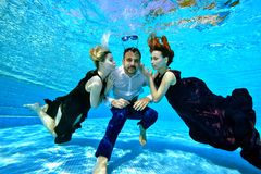 Two beautiful young girls with red and white hair swim and play with a young man in a white shirt underwater at the bottom of the stock images