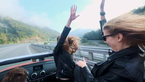 Two beautiful young girls ride in a red cabriolet among the mountains. Road on the highway. Dressed in black leather. Jackets. Hair fluttering in the wind stock footage