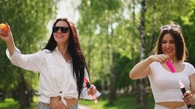 Two beautiful young girls in sexy clothes are laughing and dancing while riding a Segway in the Park on the weekend. Playing with soap bubbles in slow motion stock footage
