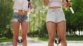 Two beautiful young girls in sexy clothes are laughing and dancing while riding a Segway in the Park on the weekend. Playing with soap bubbles in slow motion stock video footage