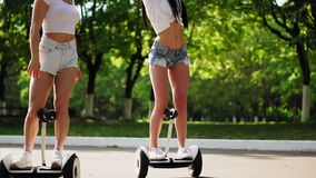 Two beautiful young girls in sexy clothes are laughing and dancing while riding on Segway in the Park on the weekend.  stock video