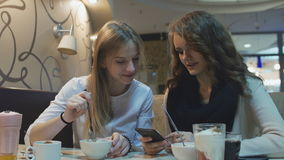 Two beautiful young girls sitting in a cafe and looking at mobile phone screen. stock video footage