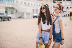 Two beautiful young girls on a skateboard in the city. royalty free stock photo