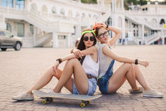 Two beautiful young girls on a skateboard in the city. Stock Image