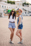 Two beautiful young girls on a skateboard in the city. royalty free stock photography